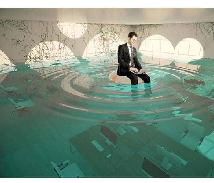 man sitting in chair and working on laptop in water covered room