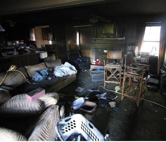 A family room covered in soot and smoke damage after a fire